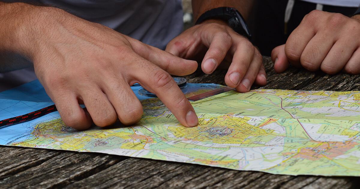 térkép körül álló, túrát tervező emberek keze a térkép felett